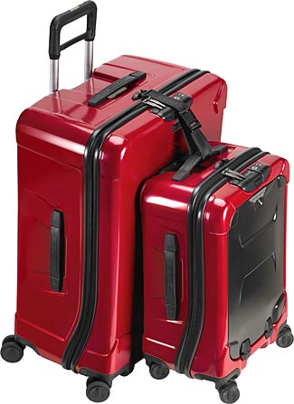 One of the larger new Briggs & Riley hard-sided suitcases with a matching carry-on strapped to it with the included connecting strap.
