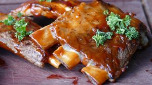 Plate of baby back ribs covered in sauce.