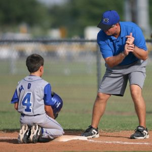 Man coaching young boy in baseball.