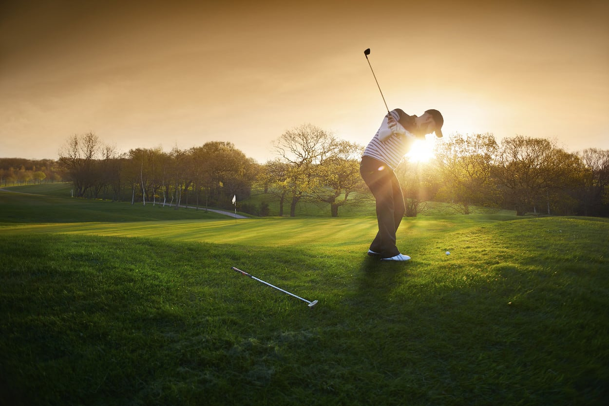 A man golfing at sunset.