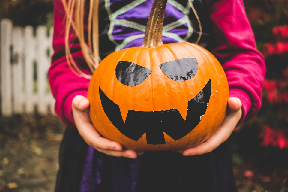 A small girl holding a decorated pumpkin while trick-or-treating.