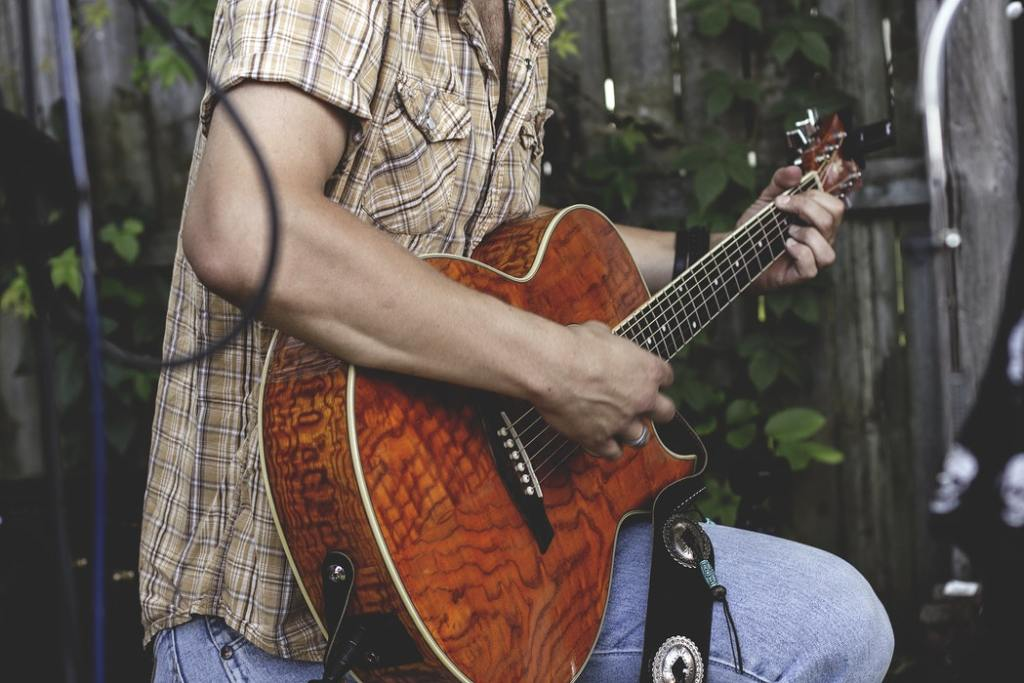 A man playing guitar at an outdoor festival.