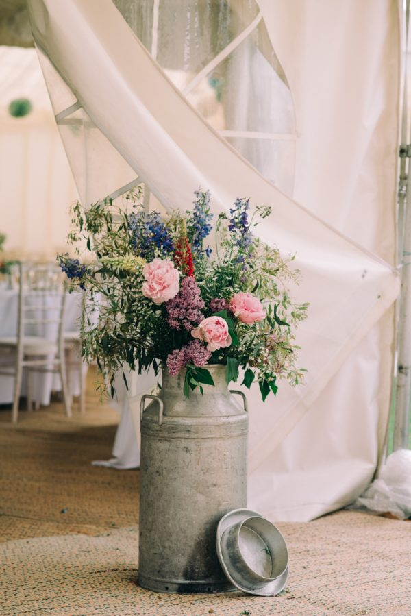 decorate marquee flowers in milk churns