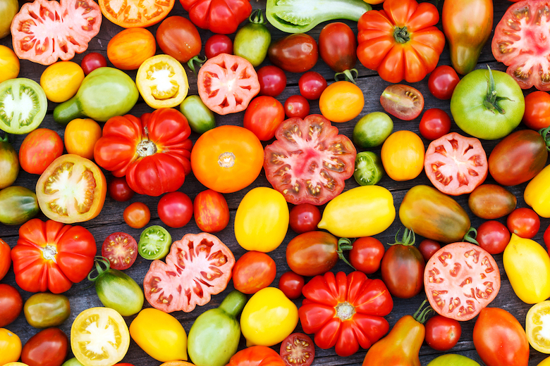 Multicoloured tomatoes lying on a wooden board