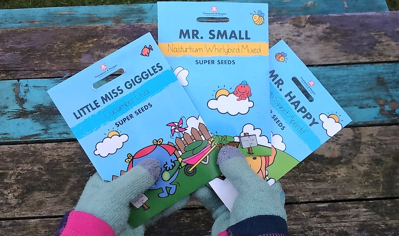 Hand holding three packs of the Mr Men/Little Miss Seed Range from Thompson & Morgan - photo by dogwooddays