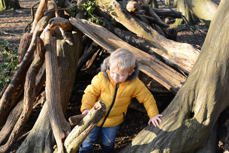 Kid in a yellow jacket playing in a forest den