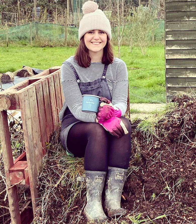Shannon wearing bright pink gardening gloves on an allotment