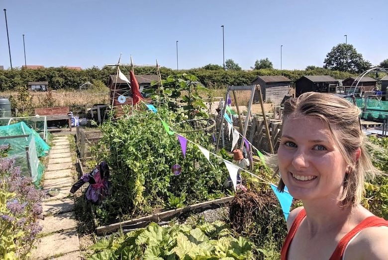 Allotmenteer Jane taking a selfie whilst overlooking her thriving allotment