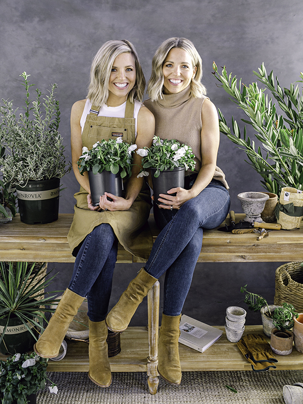 twin sisters plant ladies holding potted plants