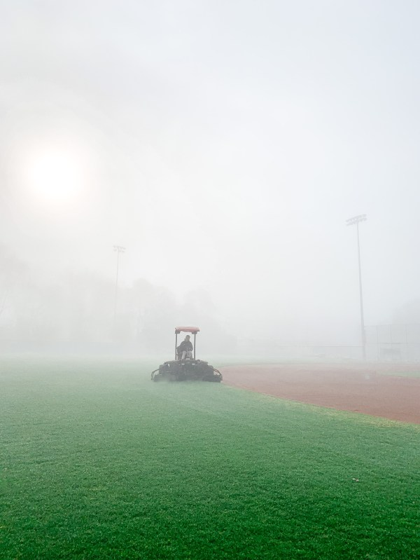 Woman driving a tractor on a field.