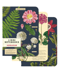 Set of 3 mini notebooks from Those Plant Ladies. Two with navy backgrounds, one with an ivory background. All 3 have greens and flowers arranged on the cover.