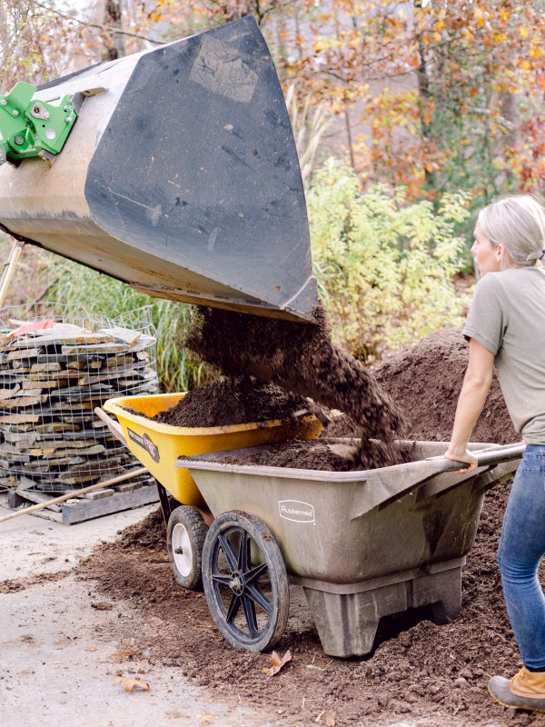 The Avant Loader 630 dumping mulch into two wheel barrows on Those Plant Ladies landscape installation.