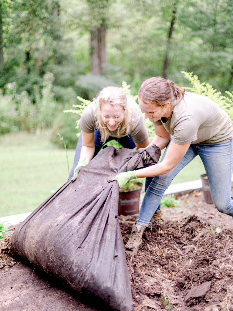 Members of Those Plant Ladies removing old mulch at an installation job site.
