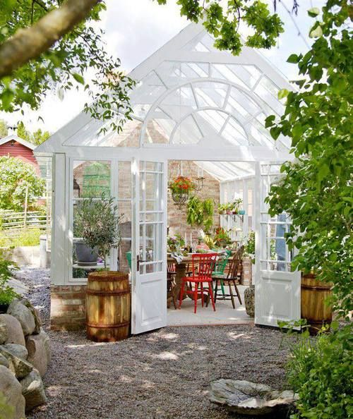 White greenhouse with the exterior doors open; sitting area inside.