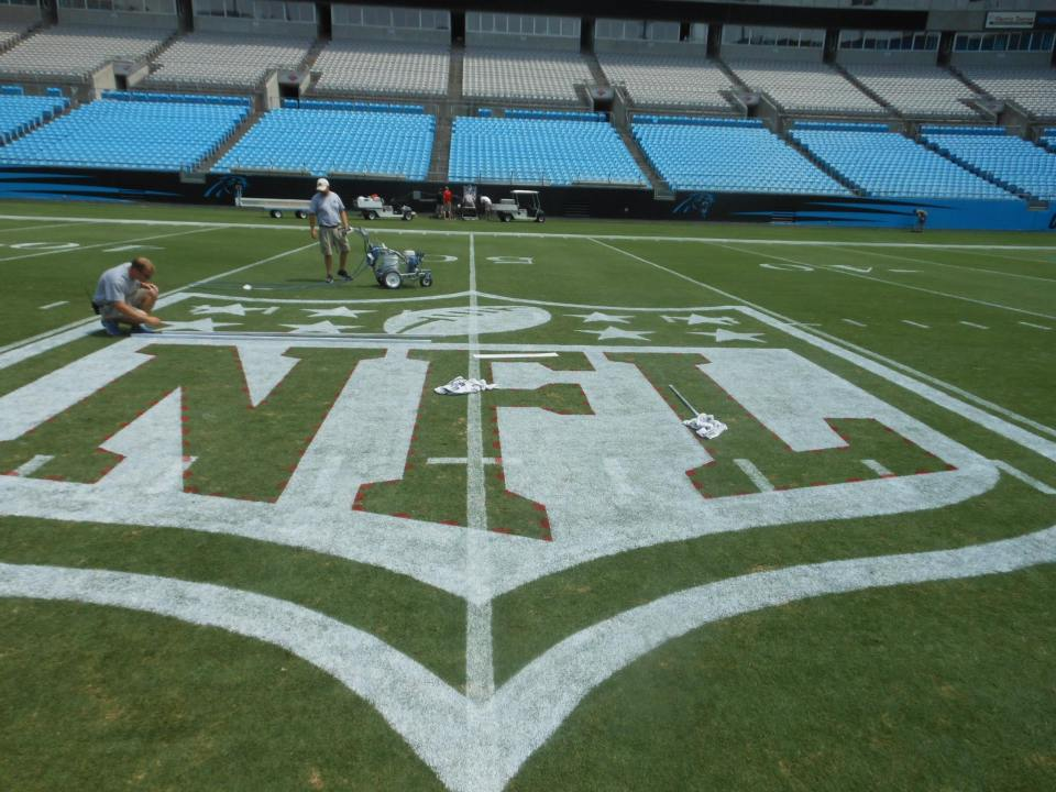 The NFL logo being painted at the Carolina Panthers' stadium.