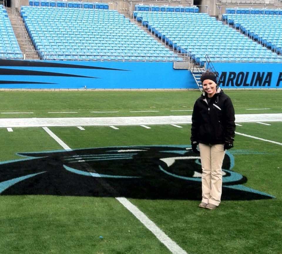 Fawn of Those Plant Ladies standing next to a Carolina Panthers logo she painted on the field.