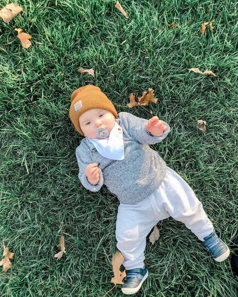A young baby in the grass as leaves start to fall.