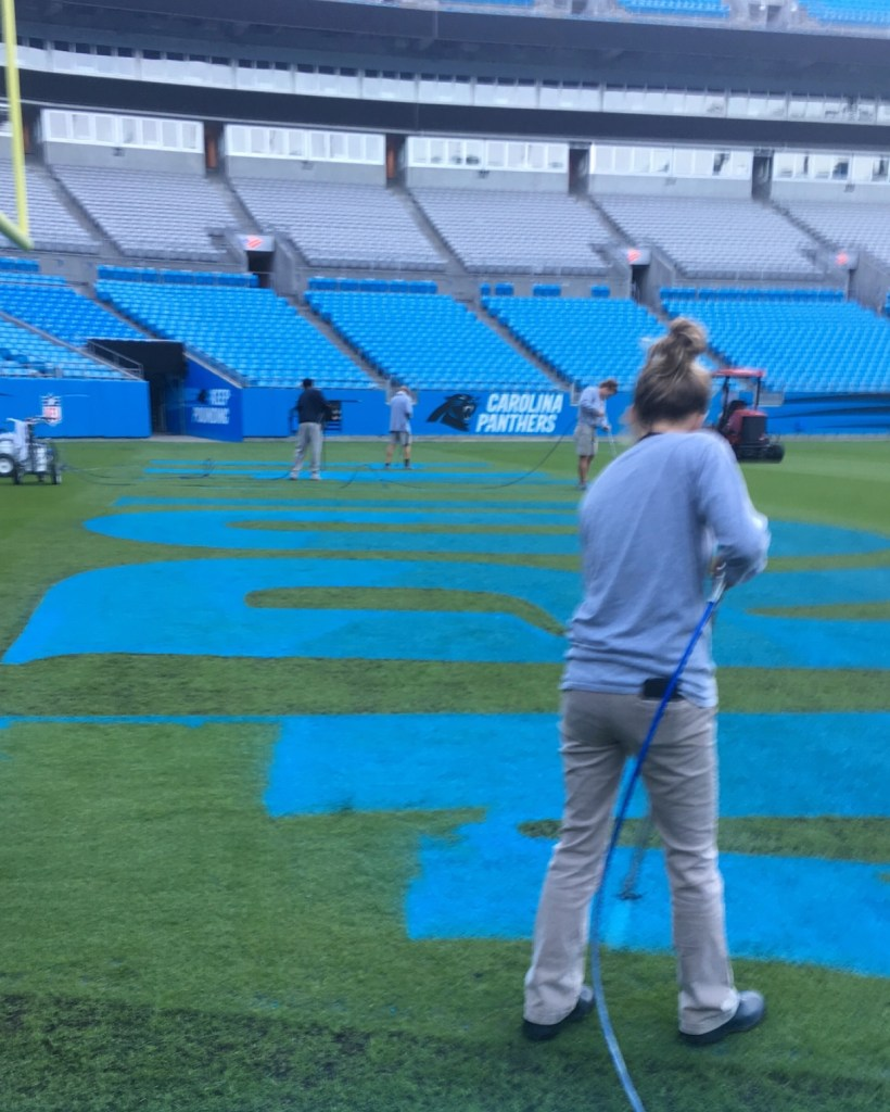 Fawn of Those Plant Ladies painting the end zone at the Panthers' stadium.