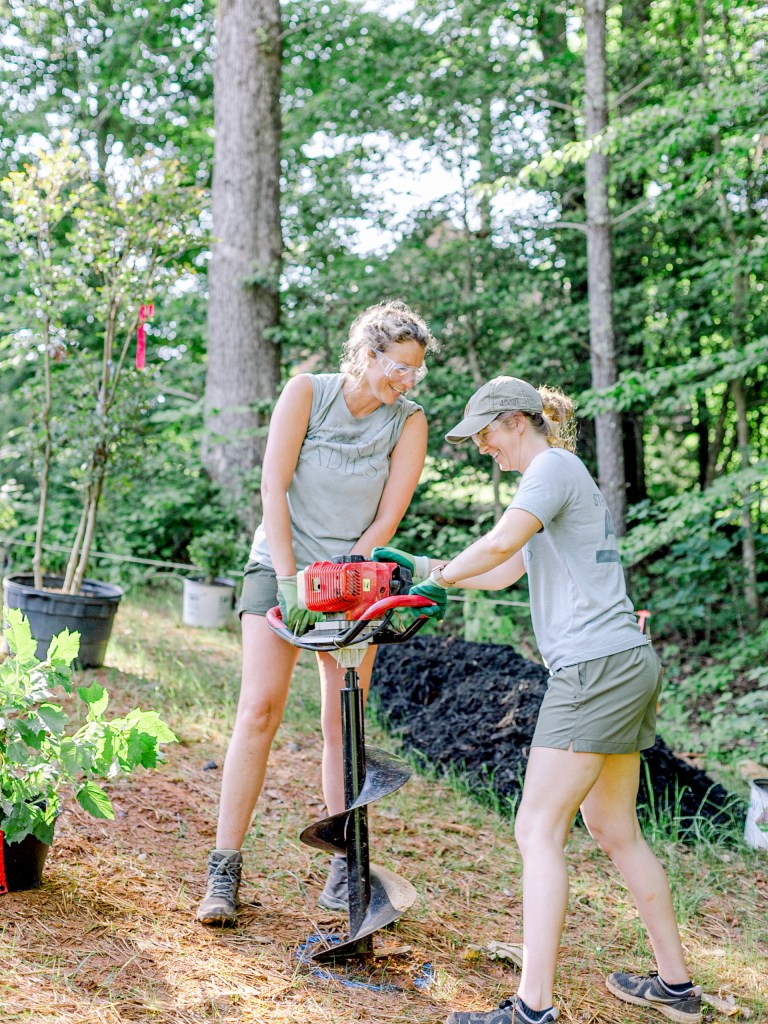 The crew of Those Plant Ladies using the auger at the landscape installation for The Blooming Estate.