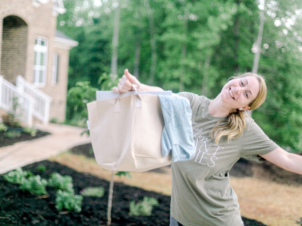 The volunteer with her gift bag at the Those Plant Ladies installation of The Blooming Estate.