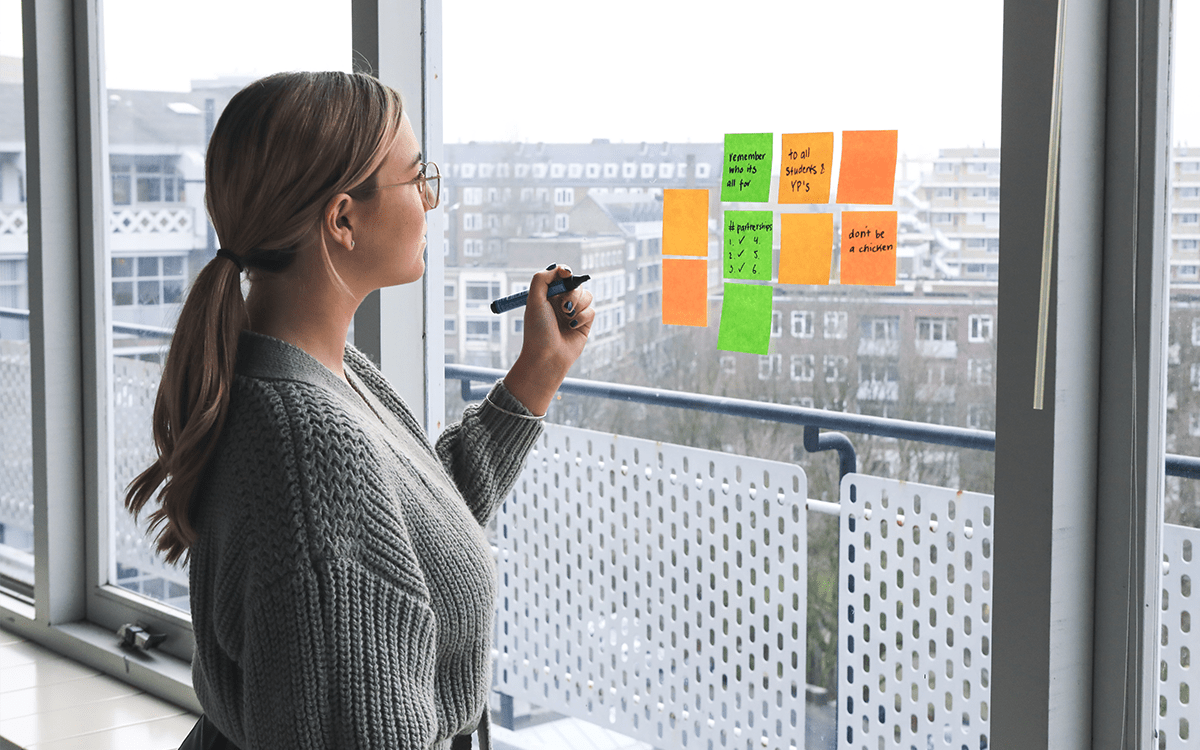 female writing her business culture plans down on sticky notes