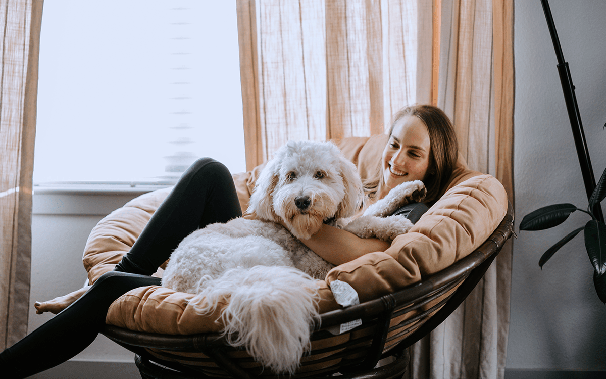 Young woman with dog relaxing while on a cozy staycation