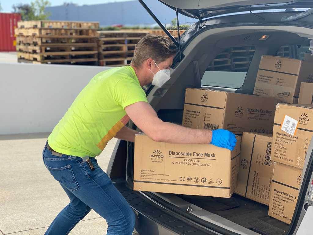Image shows a person loading car trunk with care kit, disposable face mask boxes