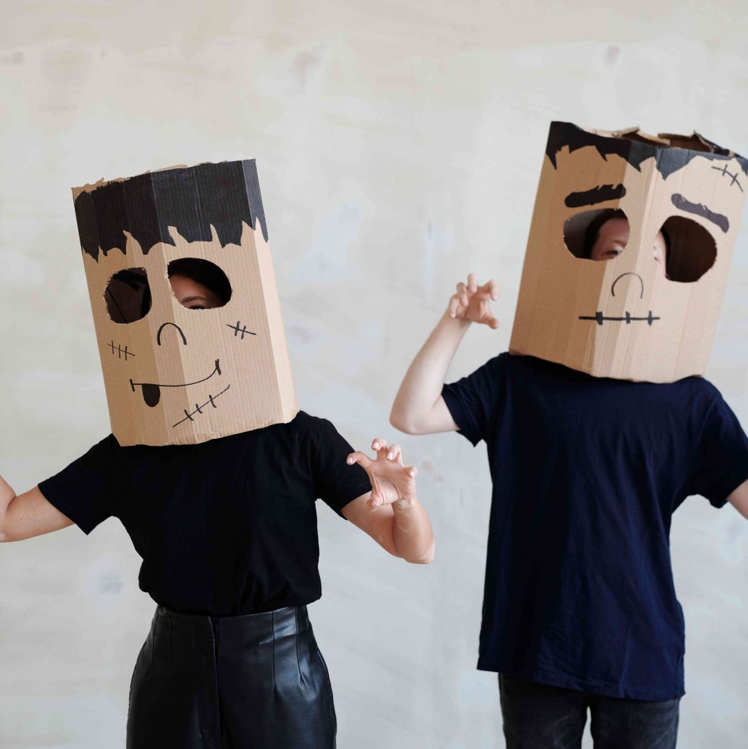 Two persons with cardboard boxes on their heads dressed as Frankensteins