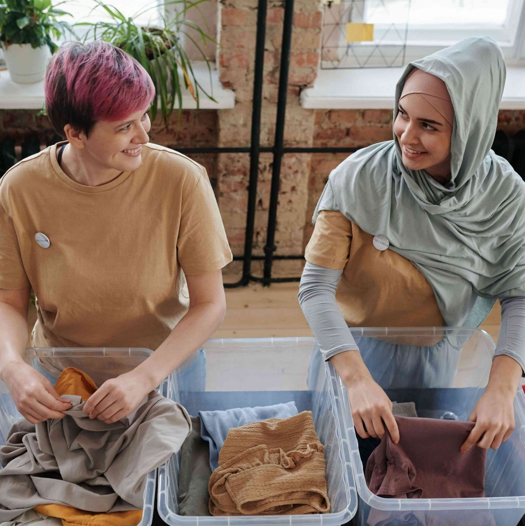 Two persons collecting clothes in plastic boxes for charity