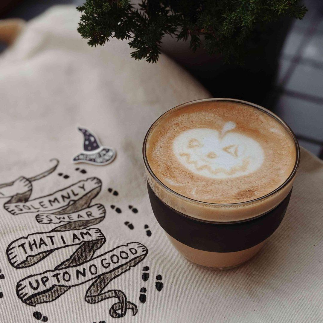 Cup of pumpkin latte with pumpkin decor