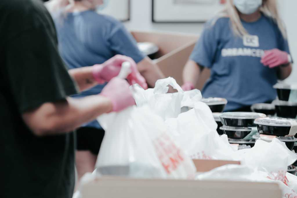 Image shows a group of people collecting food packages for homeless shelters