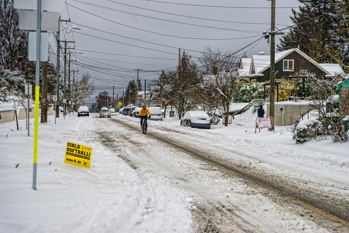 A cyclist attempts to cycle along snow-covered 28th Avenue in Magnolia, Seattle (February 13, 2021).