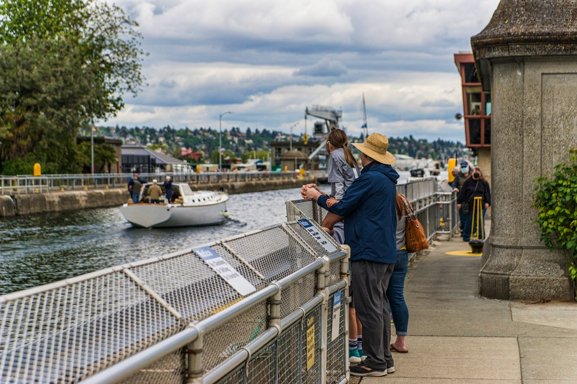 A family observes a boat sailing through the Ballard Locks in Seattle. (May 8, 2021)
