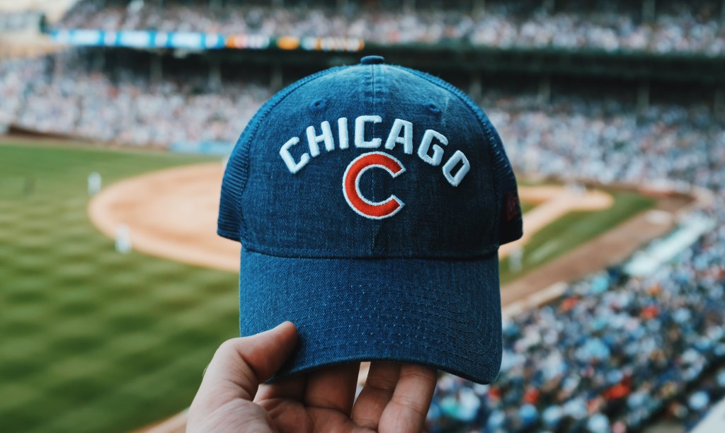 Cubs baseball cap held up in front of Wrigley Field