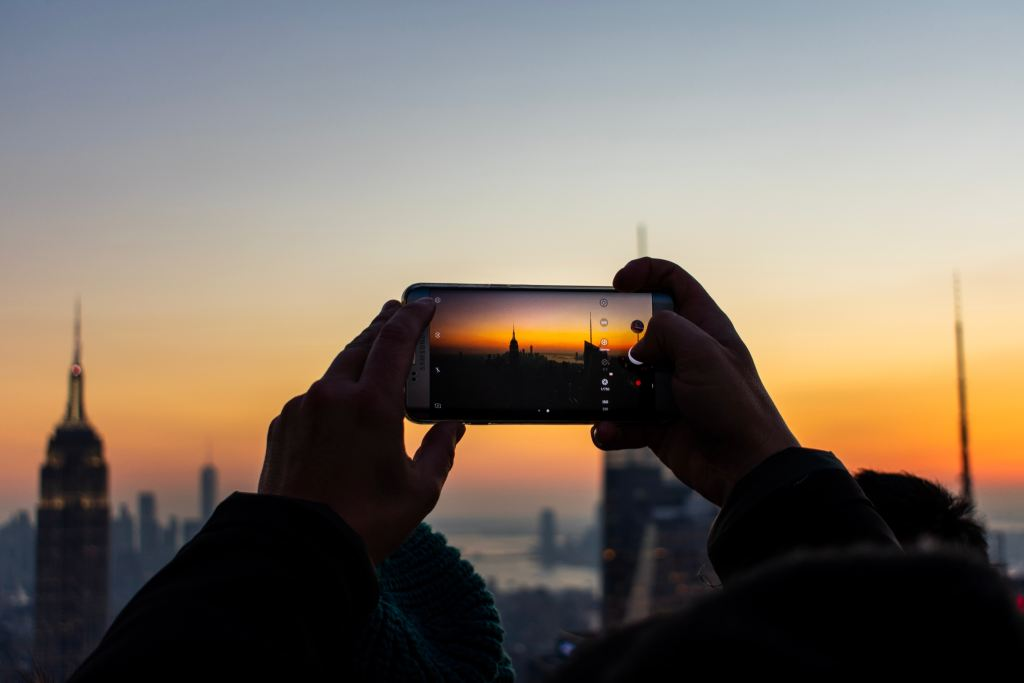 Hands holding an iPhone take a photo of the New York City skyline from the top of the Rockefeller Center at sunset.