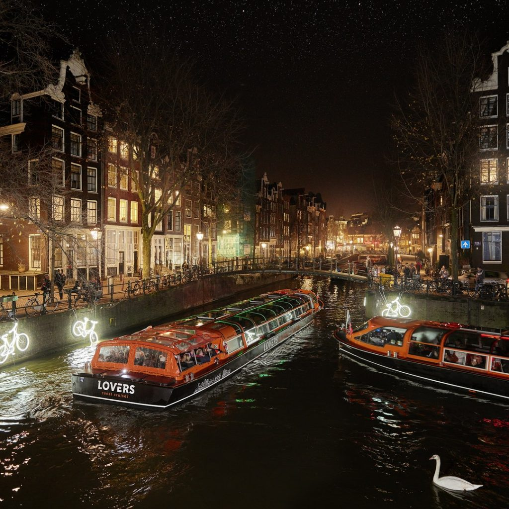 Boats from Lovers Canal Cruises navigate an Amsterdam canal during the Amsterdam Light Festival.