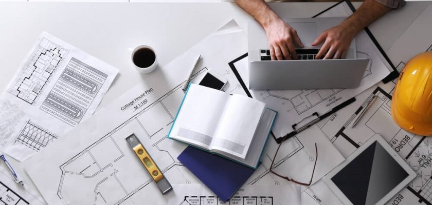 Top view image of a person fiddling with a notebook on a table, to exemplify the importance of construction planning.