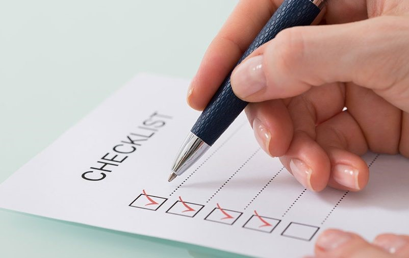 """female hands holding a pen on a paper with the term """"checklist"""" printed on it."""
