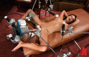 Beautiful brunette is naked and pampered with two Hitachi toys on each nipple and two on her cunt