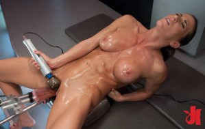 Muscular woman takes two fucking machines in her cunt, one up her ass and rubs her clit also