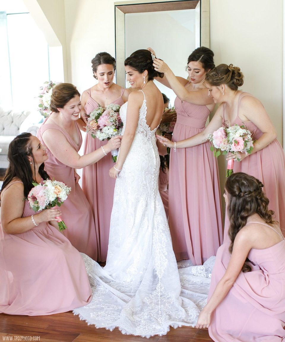 Bridesmaids in pink dresses adjusting the bride's dress in the Bridal Suite at a Rosewood Farms Maryland Wedding
