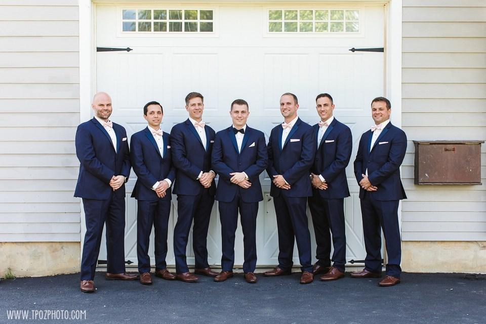 Groomsmen in navy suits and pink bow ties