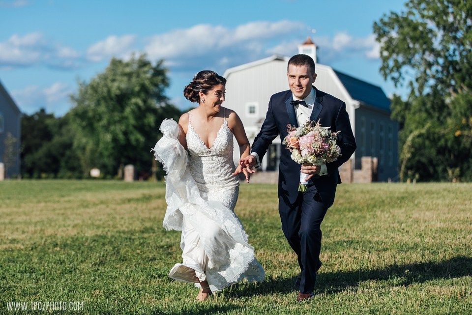 Bride and groom racing in front of the Rustic Barn.