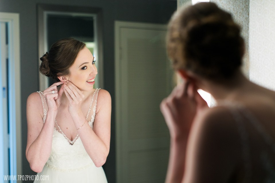 Bride putting earrings on