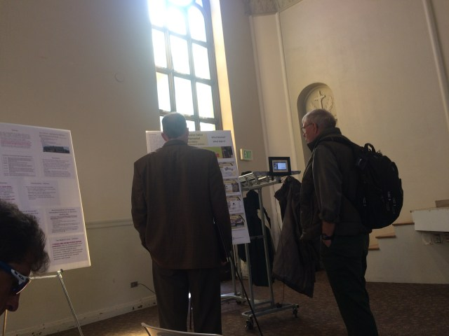 Conference goers looking at my poster