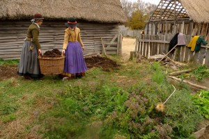 "Women tending a garden in the English Village of Plimoth Plantation. In the foreground are some plants they use to make ""infusions."""