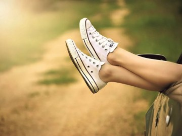 girls legs hanging out car window wearing converse