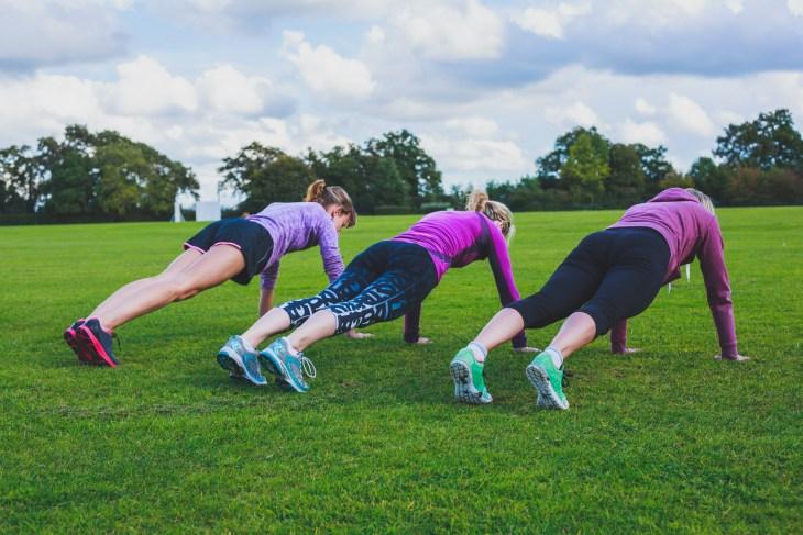Three women doing push ups in park