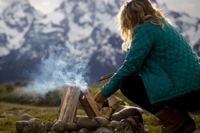 Woman Setting Up Campfire