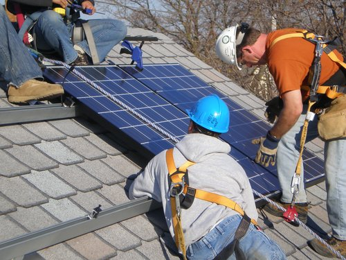 Workers installing solar panels on a Milwaukee residence